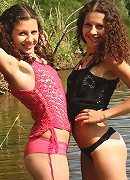 Two girls strip each other outdoors