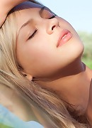 Cheerful blonde with subtly erotic poses and nubile allure.